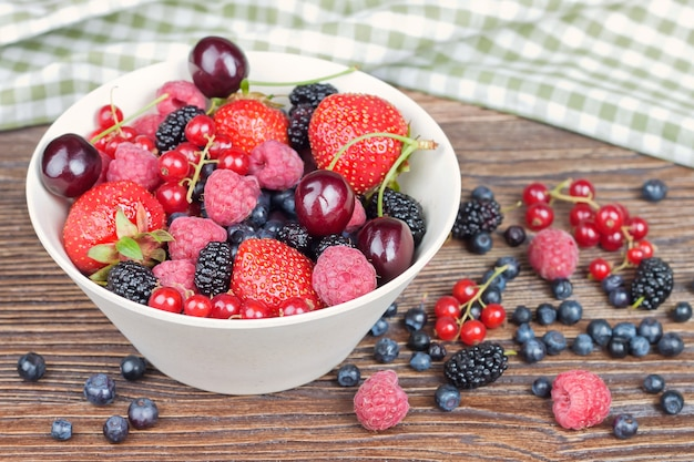 Mixed berries in a bowl on brown wooden table