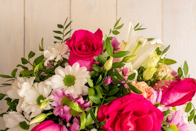 Mixed bouquet of different flowers on a wooden background