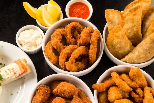 Смешанные бразильские закуски, включая выпечку, жареную курицу, салаты, супы, картофель фри и кибе.