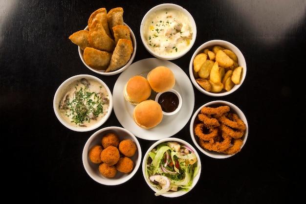 페이스트리, 프라이드 치킨, 샐러드, 수프, 감자 튀김 및 키베를 포함한 혼합 브라질 스낵