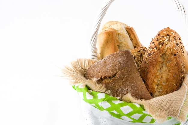 Mixed bread in a basket isolated on white wooden background copy space