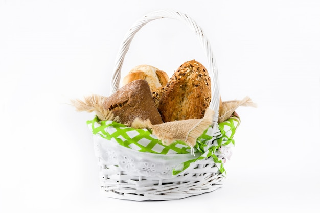 Mixed bread in a basket isolated on white wooden background