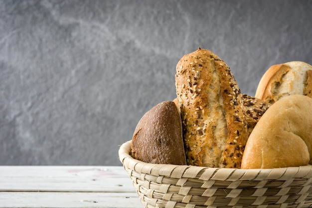 Mixed bread in basket on white wooden table