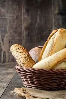Mixed bread in basket on wooden table
