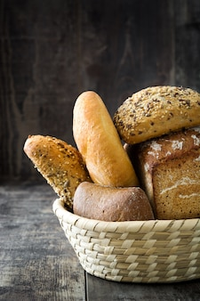 Mixed bread in a basket on wooden table