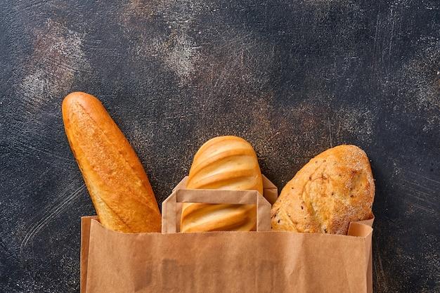 茶色の古いコンクリートの背景のテーブルの上の紙袋の混合パン。コピースペース付きの上面図フラットレイ