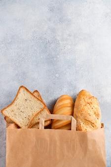 ライトグレーのコンクリートの石のテーブルの上の紙袋の混合パン。コピースペースのある上面図。