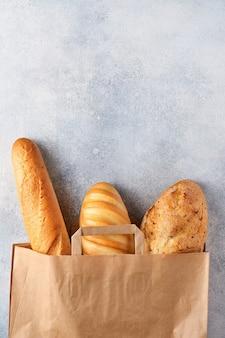ライトグレーのコンクリートの石のテーブルの上の紙袋の混合パン。