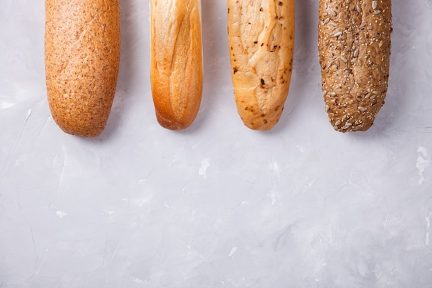 Смешанные хлебы на светлой предпосылке, взгляд багетов взгляд сверху с космосом экземпляра селективный фокус.