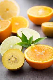 Смесь цитрусовых лимонов, апельсина, киви, лайма на сером