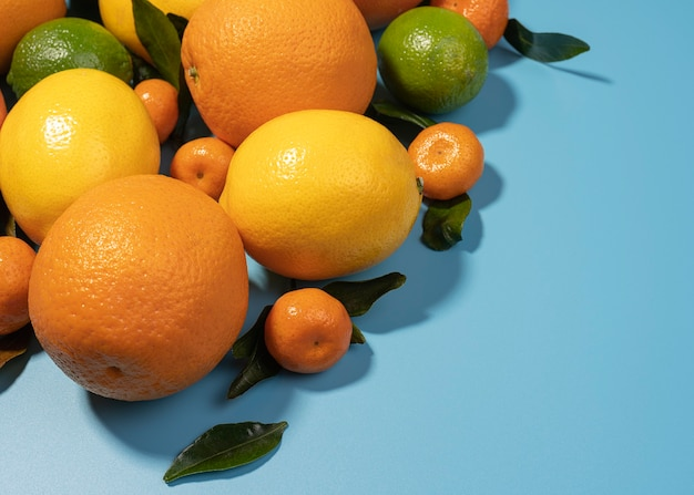 コピースペースと青い背景の葉と混合柑橘系の果物