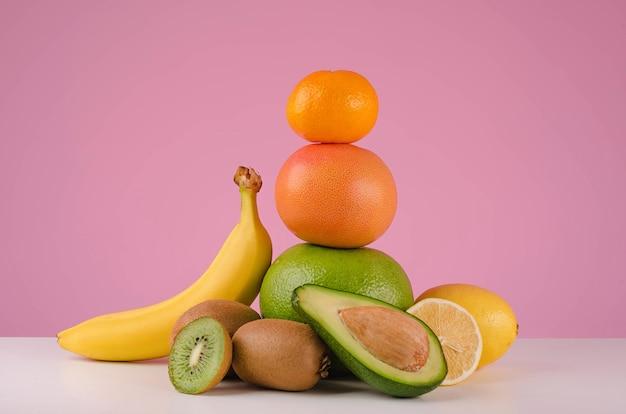 ピンクの背景で隔離のテーブルにレモン、グレープフルーツ、ザボン、みかん、バナナ、アボカドなどの混合柑橘系の果物