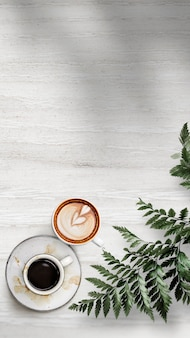 Mixed coffee cups with a leaf on a white wooden textured wallpaper