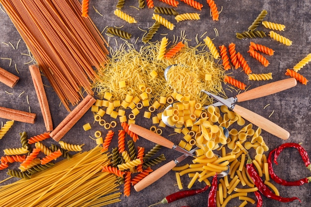 Mixed color pasta with spoon fork pepper on gray surface