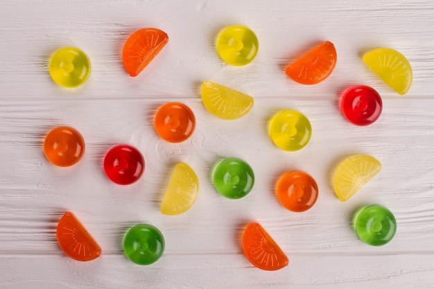 白い背景の上の混合カラフルなキャンディー。さまざまな形や色のお菓子。上面図