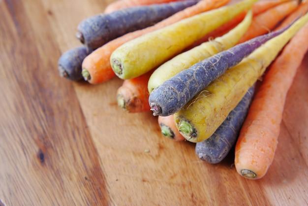 Смешанная красочная морковь на разделочной доске