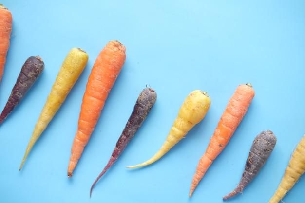 Смешанная красочная морковь на синем фоне
