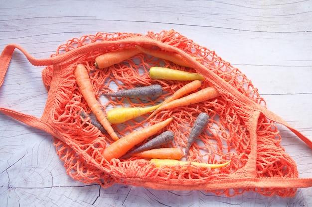 Смешанная красочная морковь и хозяйственная сумка на деревянном фоне