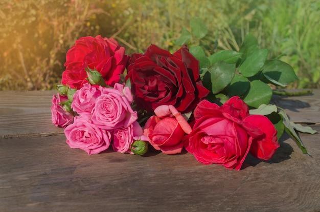 満開の色とりどりのバラが混ざり合っています。美しさのバラの花。木製の背景に楽しい花。