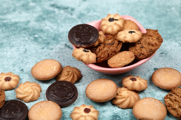 Mixed cookies in a pink bowl.