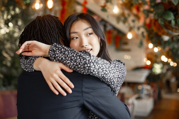 카페에서 약혼을 축하하고 단단히 포옹하는 혼합 된 커플