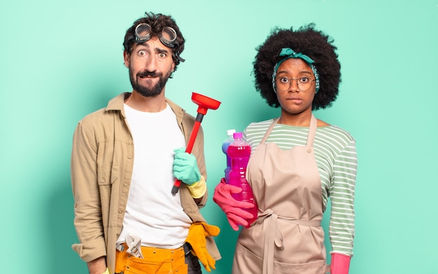 Mixed couple looking puzzled and confused, biting lip with a nervous gesture, not knowing the answer to the problem. housekeeping concept.. home repairs concept