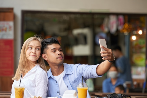 Mixed couple taking selfie