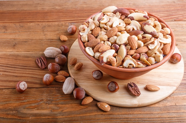 Mixed different kinds of nuts in ceramic bowl on brown wooden background with copy space.