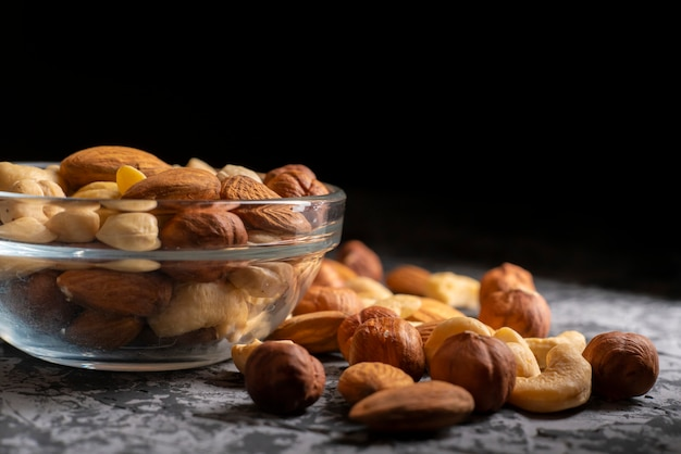 Mixed different raw cocktail nuts in a bowl on a dark table, healthy and organic food