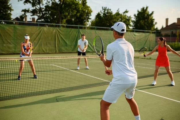 混合ダブルステニストレーニング、屋外コート。アクティブで健康的なライフスタイル、人々はラケットとボールでスポーツゲームをする、ラケットでフィットネストレーニングをする