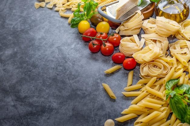 木製の背景に混合乾燥パスタの選択。黒い石の背景、トップ ビュー、フラット レイアウトに分離された健康食品成分の組成