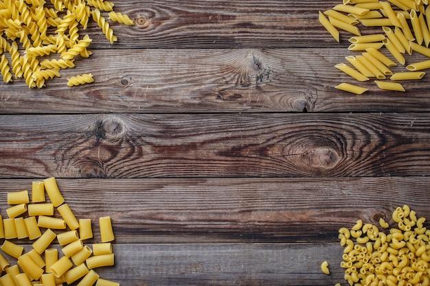 Выбор смешанных сушеных макаронных изделий на деревянных фоне. плоский вид сверху с copyspace для текста, логотипа или другого.