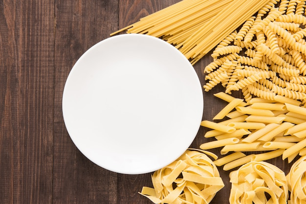 Mixed dried pasta selection on wooden background, copy space, top view.
