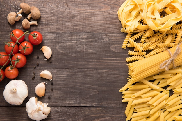 Mixed dried pasta selection on wooden background