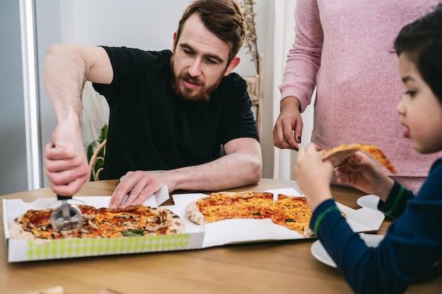집에서 천연 재료로 비건 피자를 먹는 혼합 가족. 비건 음식. 다양성과 실제 사람