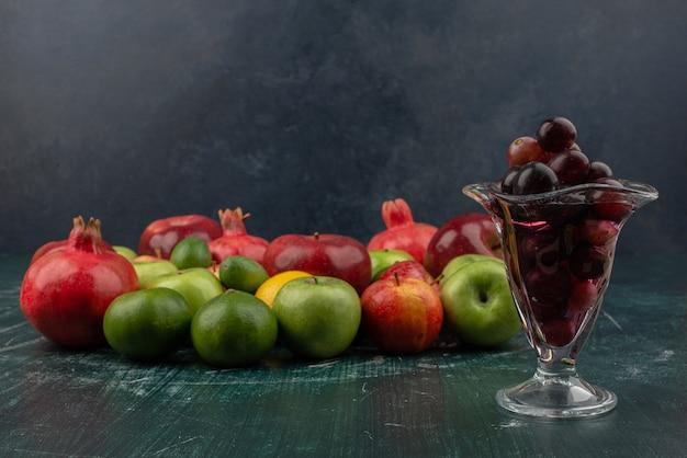 Смешанные свежие фрукты и стакан черного винограда на мраморном столе.