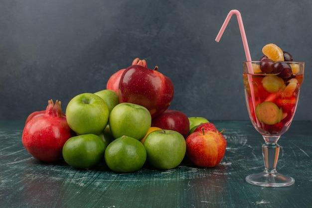 Смешанные свежие фрукты и стакан сока на мраморном столе.
