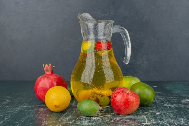 Frutta fresca mista e bicchiere di succo sul tavolo di marmo
