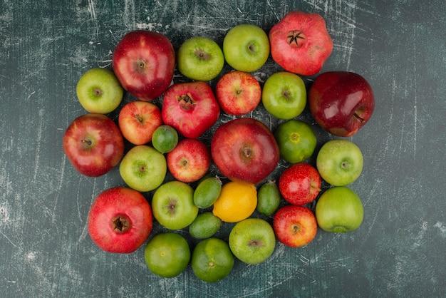 Frutta fresca mista sparsa sulla superficie di marmo.