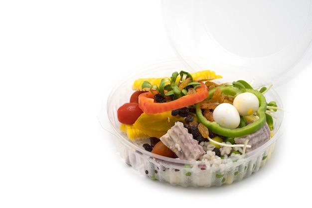 흰색 배경에 격리된 투명한 플라스틱 그릇에 혼합된 신선한 샐러드