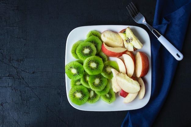Смешанные фрукты свежие киви и яблоки с виноградом в тарелку на деревянном столе.