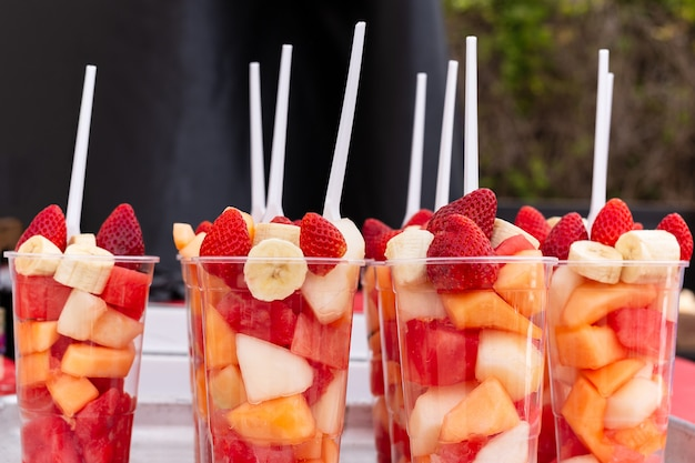 Mixed fruit salad arranged in plastic cups on a market stall.