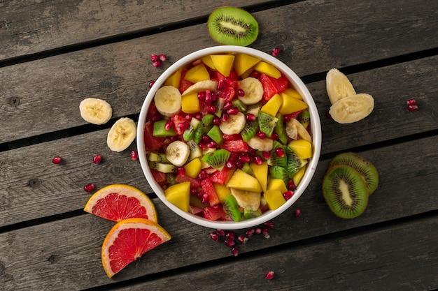 Смешанный фруктовый салат в тарелке на деревянной вид сверху концепция диета летняя еда