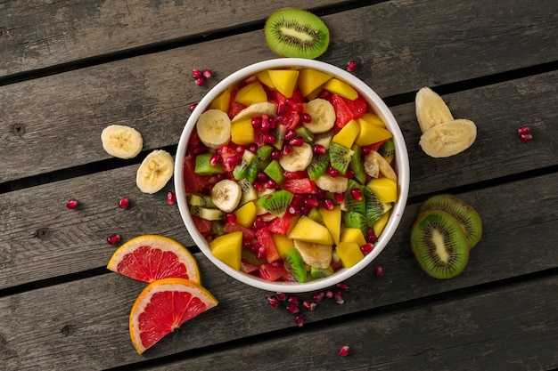Mixed fruit salad in plate on wooden top view diet summer food concept