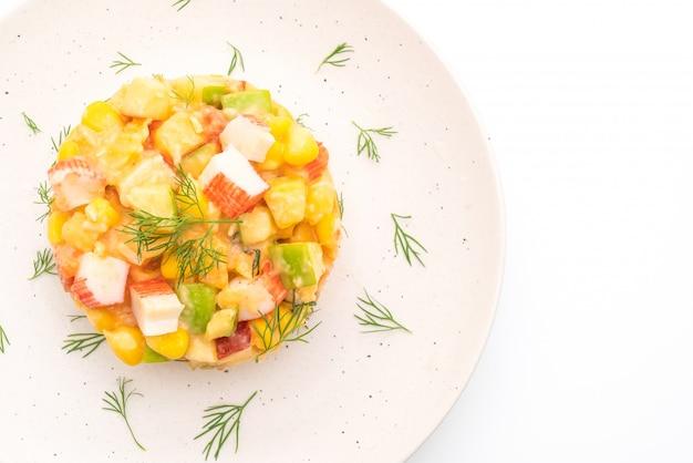 白で隔離されるカニスティック(リンゴ、トウモロコシ、パパイヤ、パイナップル)と混合フルーツサラダ