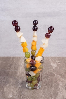 대리석 테이블에 유리에 혼합 과일 스틱.