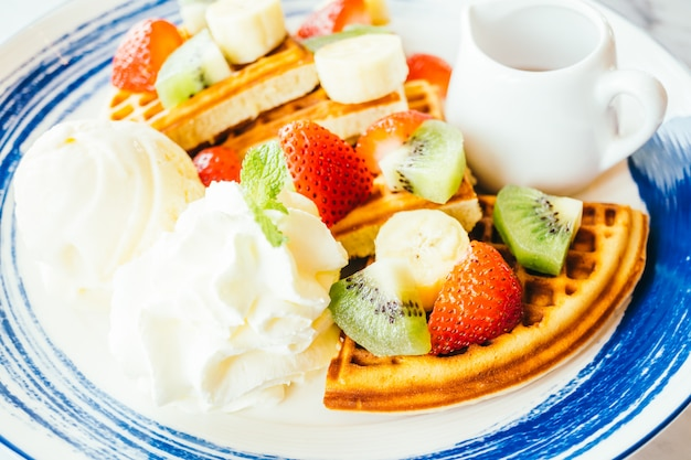 Mixed fruit on top of pancake and ice cream