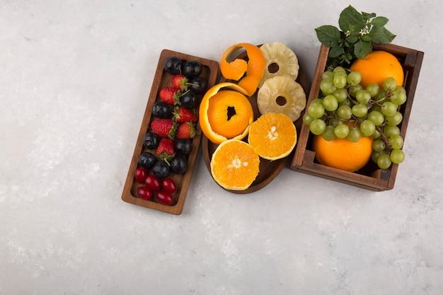 中央の木製の大皿にミックスフルーツとベリー