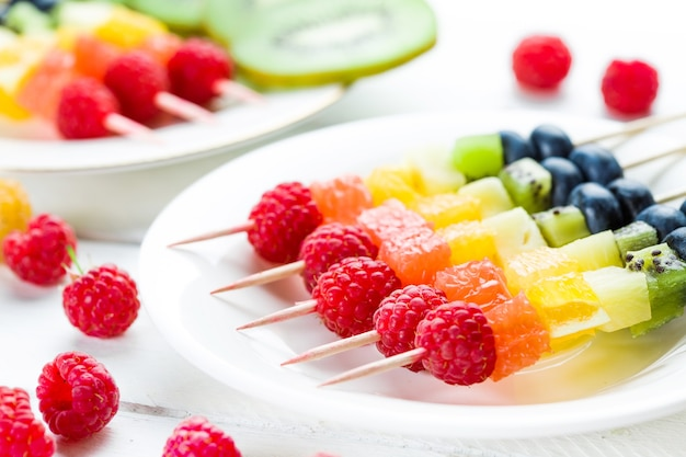 Mixed fruits and berries on white wooden table.