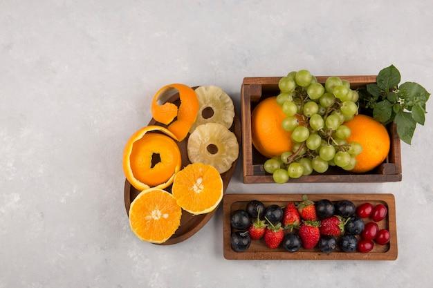 Frutta mista e bacche in vassoi di legno su uno spazio bianco